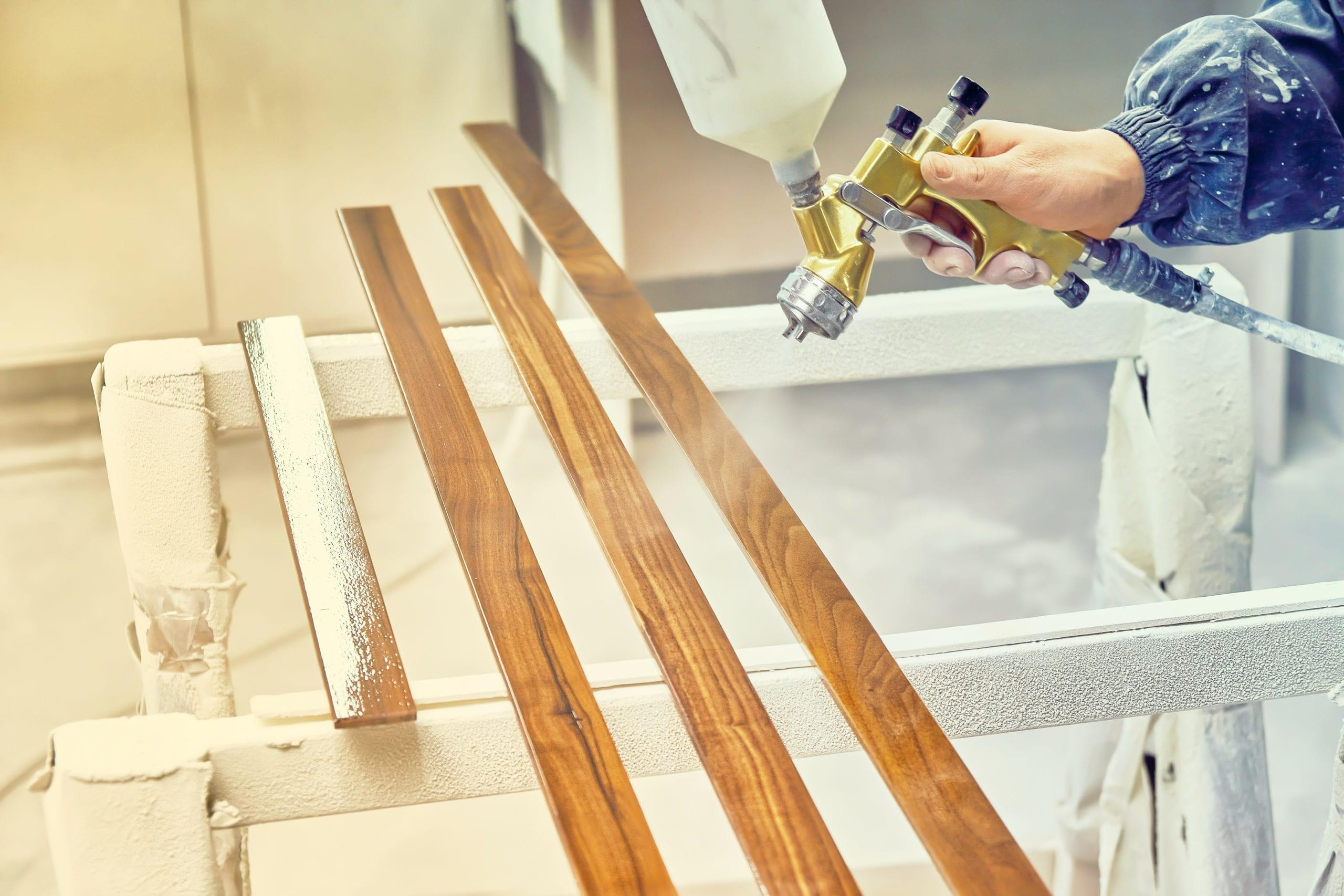 Man Painting Furniture Details In A Spray Booth. Worker Using Spray Gun.